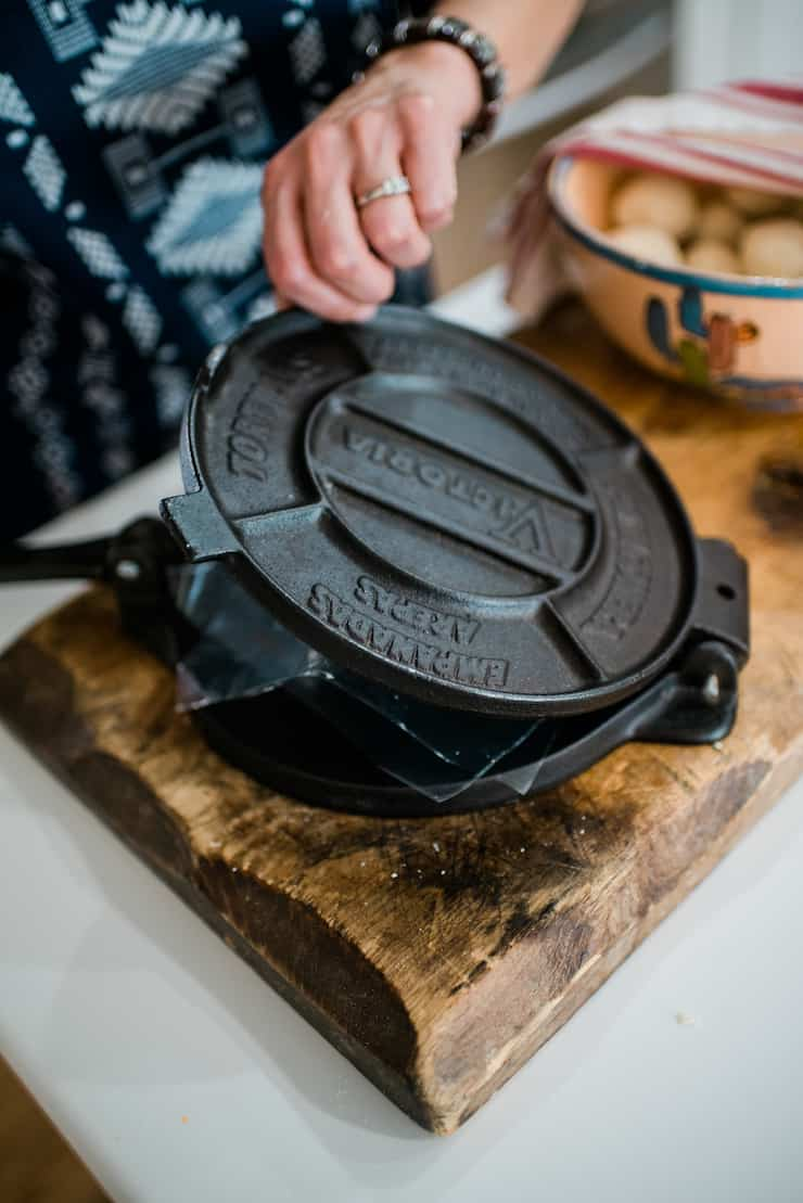 Cast Iron Tortilla Press on a wooden cutting board with a bowl in the background filled with dough balls to make corn tortillas