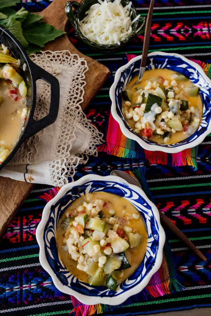 Calabacitas con Elote or Zucchini with Corn served in two bowls on a table covered with a beautiful cloth