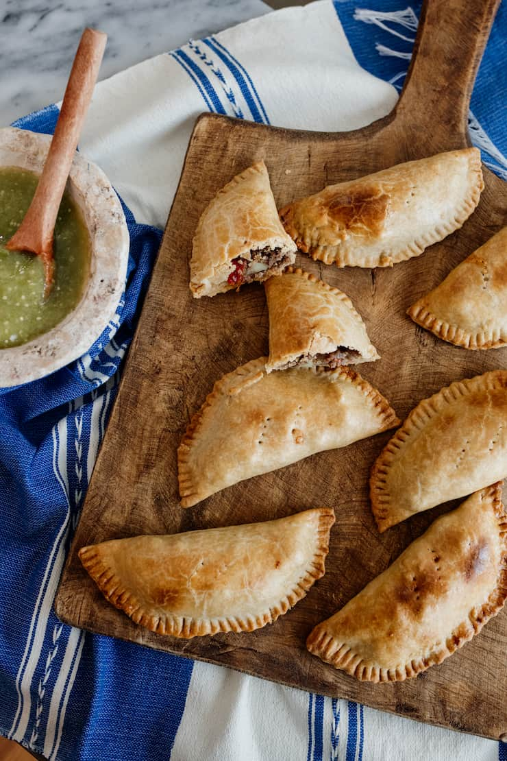 Mexican Picadillo Empanadas on a wooden board with a side of salsa verde on a blue Mexican linen