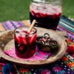 Agua de Jamaica or Hibiscus Tea served in a glass with a big jar next to the tray