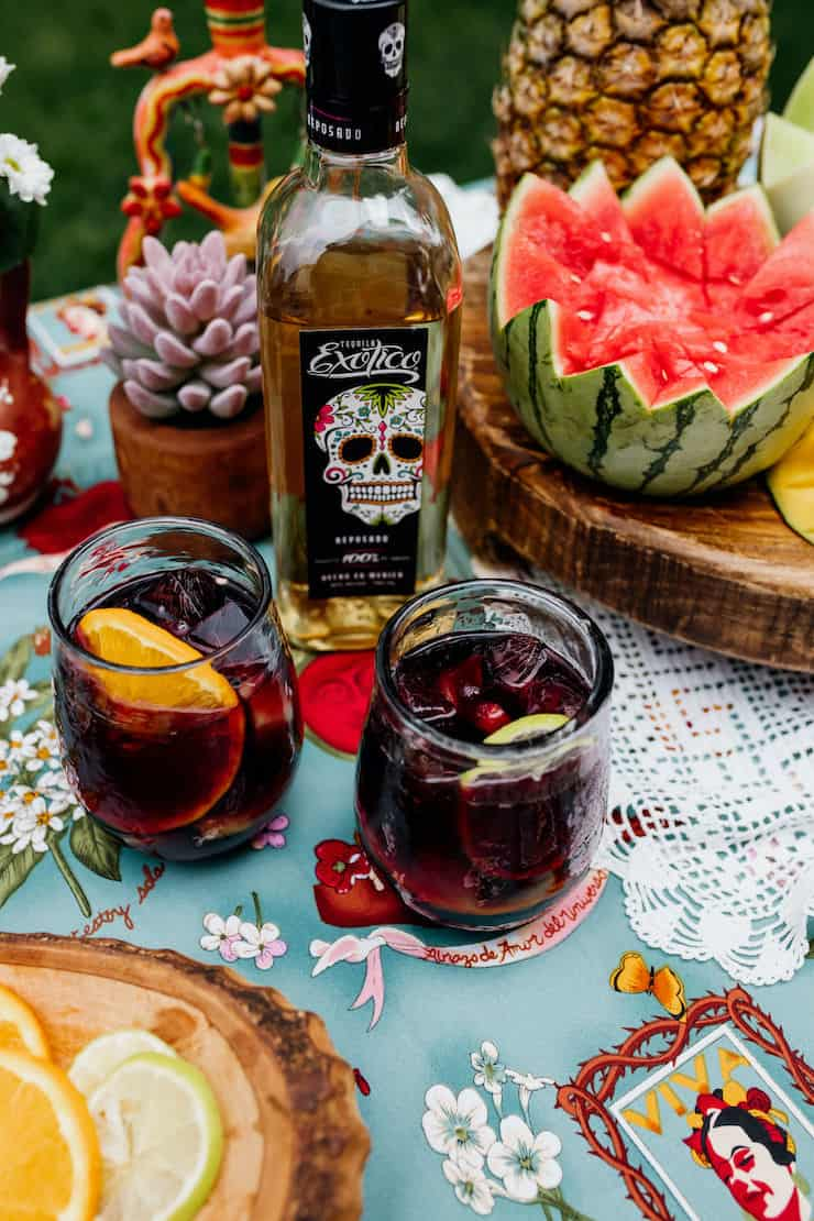 tequila infused sangria recipe in two glasses with a bottle of Exotico tequila in the background