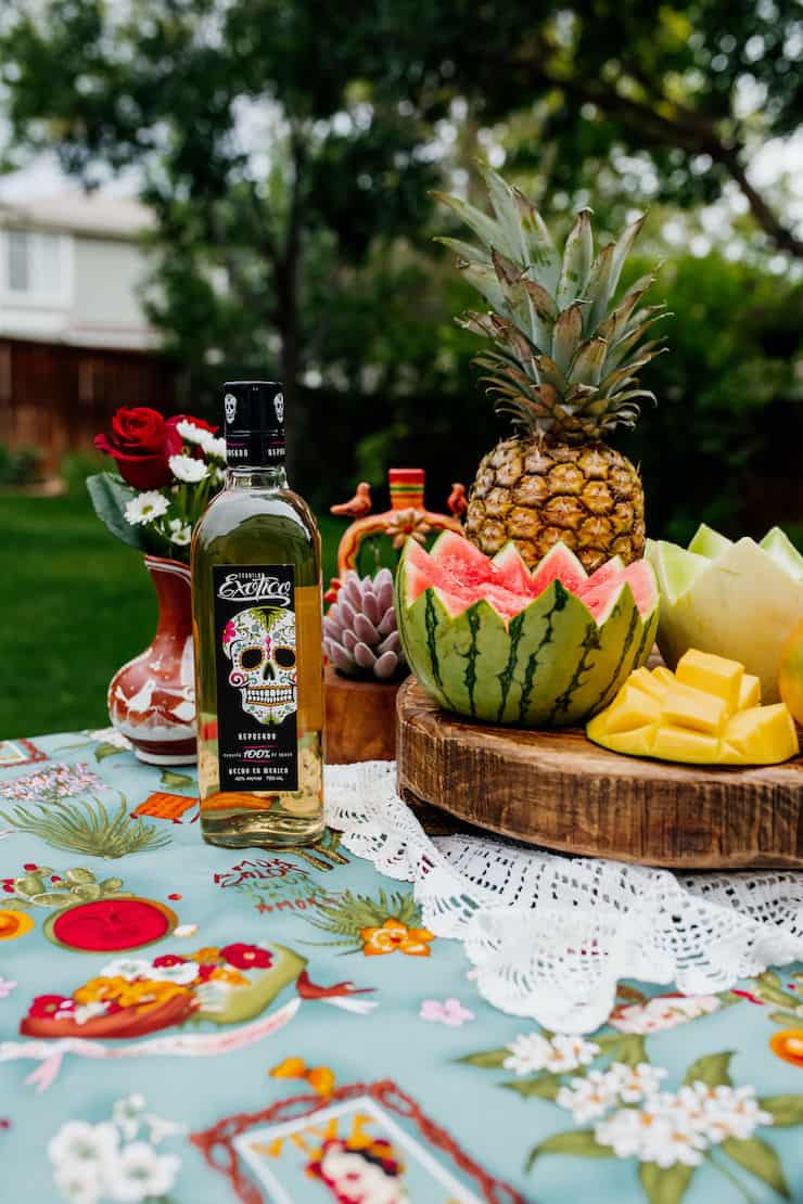 exotic tequila bottle with melons and a pineapple on a wooden pedestal on a white doily and teal tablecloth outside
