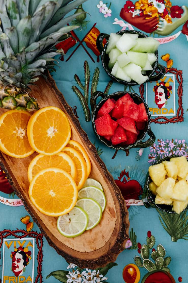 slices of limes and lemons in a wooden bowl and chopped fruit in small bowls