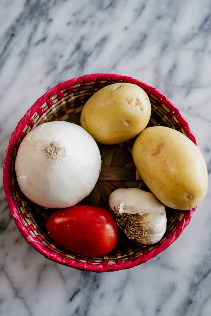 Mexican palm basket on a marble surface filled with a Roma tomato, onion, garlic and two potatoes