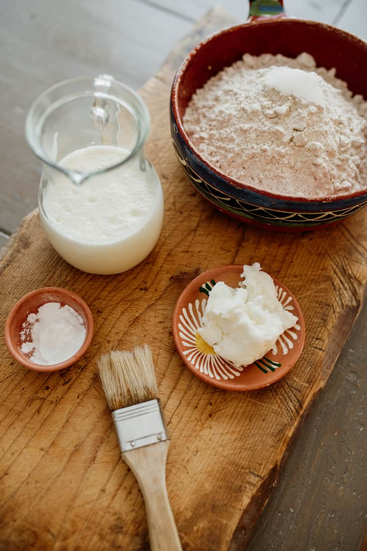 suero (buttermilk), baking powder, shortening, flour and a pastry brush on a wooden board