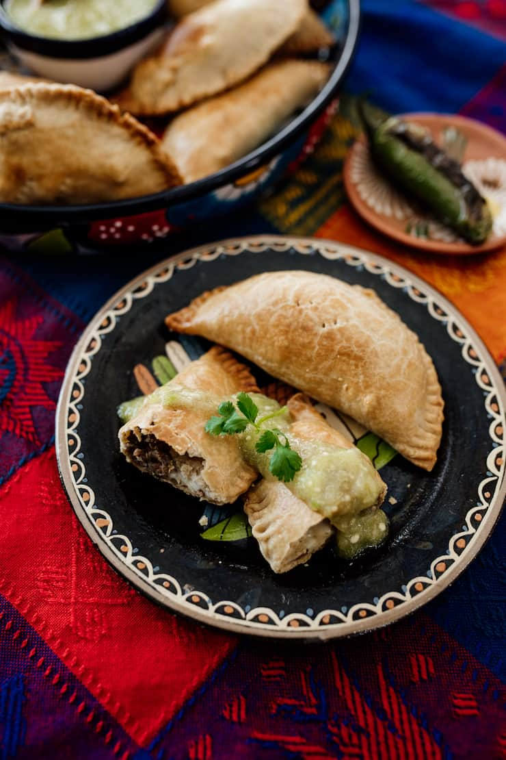 open empanada on a Mexican black plate filled with Mexican picadillo drizzled with salsa verde