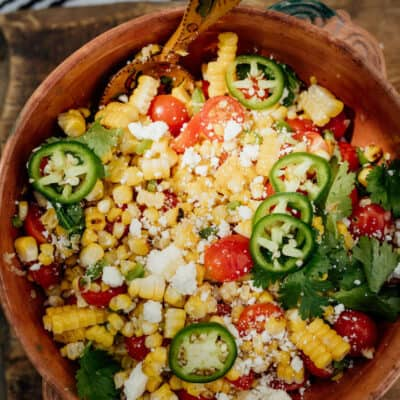 Mexican Street Corn Salad ready and served in a big bowl on a wooden board