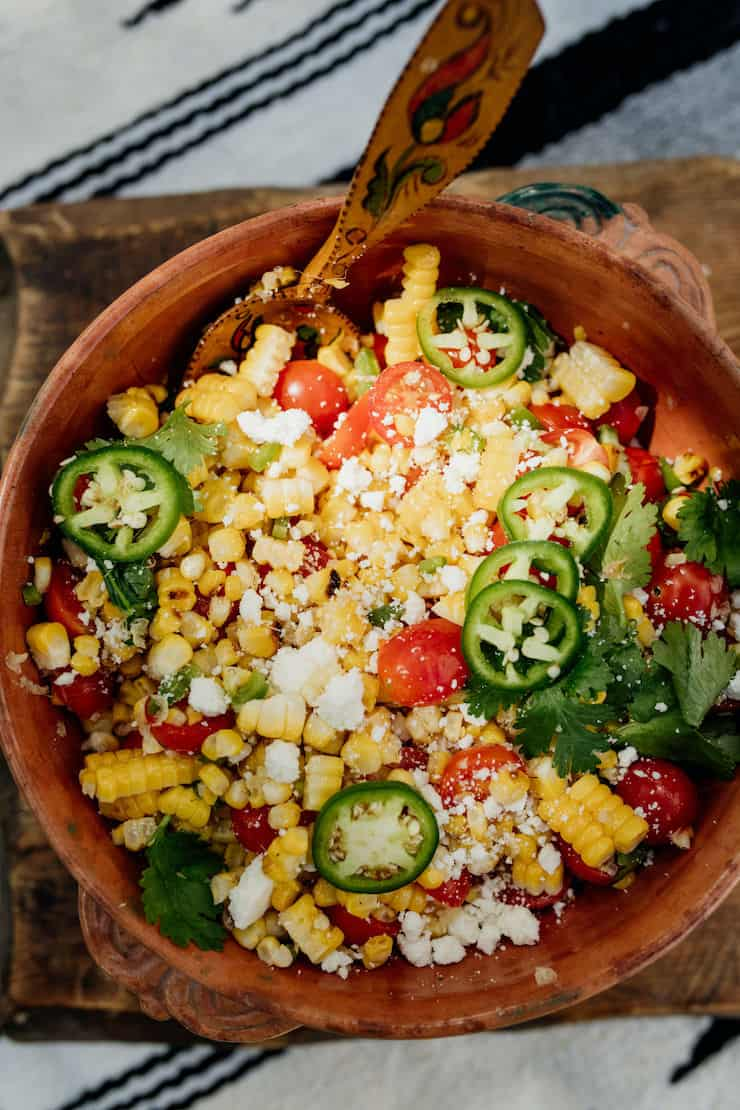 Mexican Street Corn Salad in a brown bowl with a painted wooden spoon