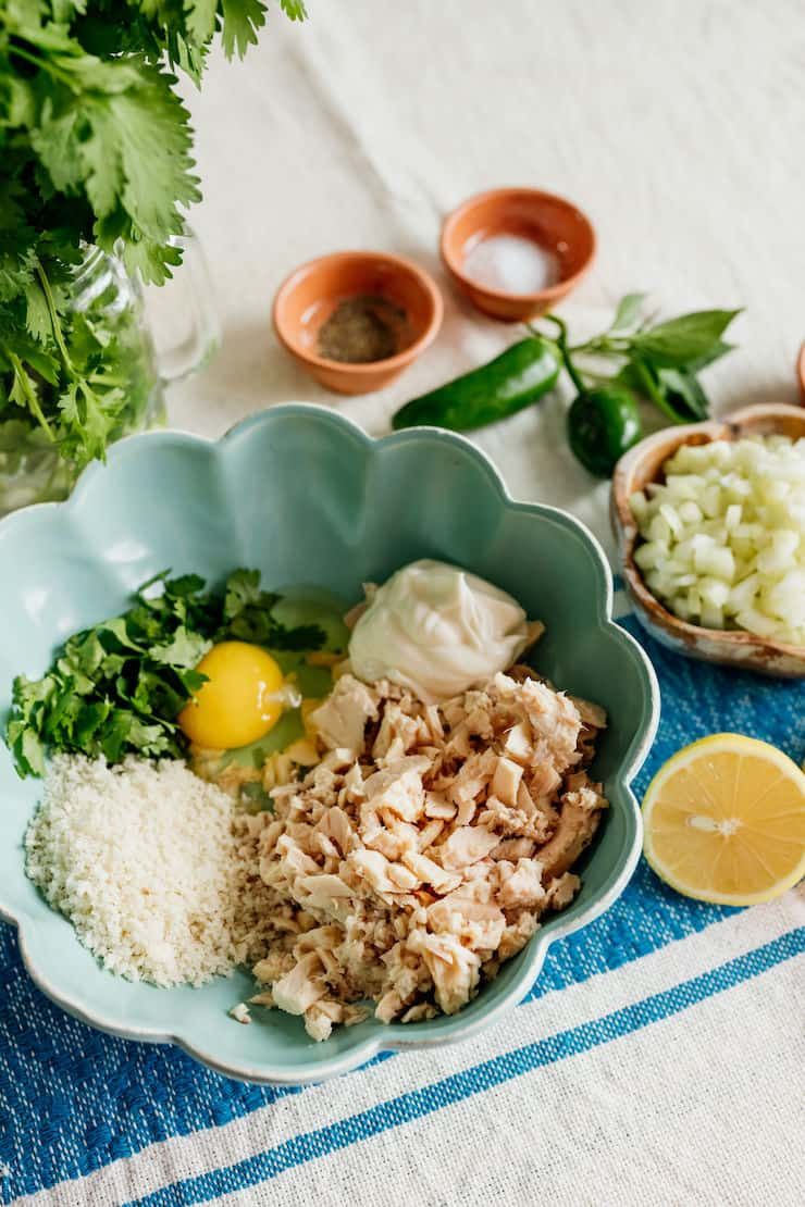 ingredients to make tuna patties - tuna, Panko, mayonnaise, eggs, cilantro, celery and lemon in a bowl