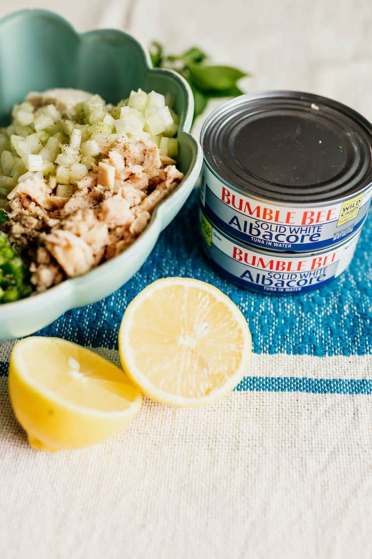 2 cans of solid white albacore tuna with a bull of ingredient to make a muster for tuna patties and a lemon the side