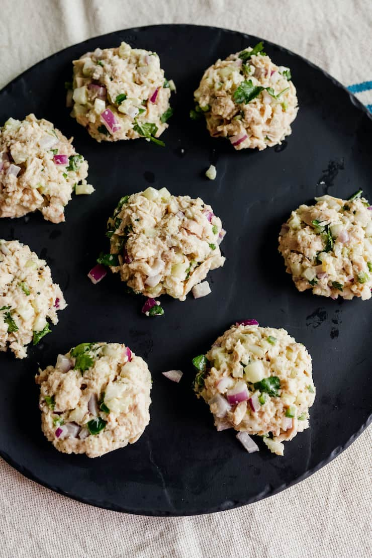 tuna patties formed and on a black plate on a Mexican white runner