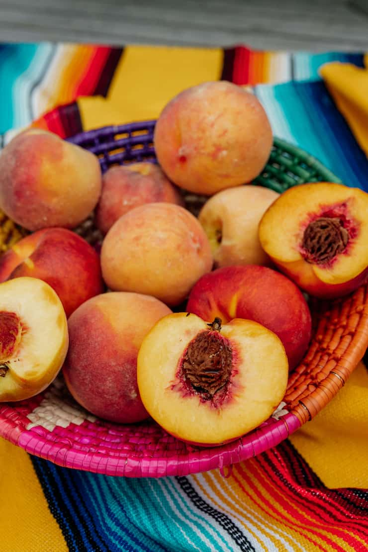 multicolored basket filled with peaches, some of which are halved