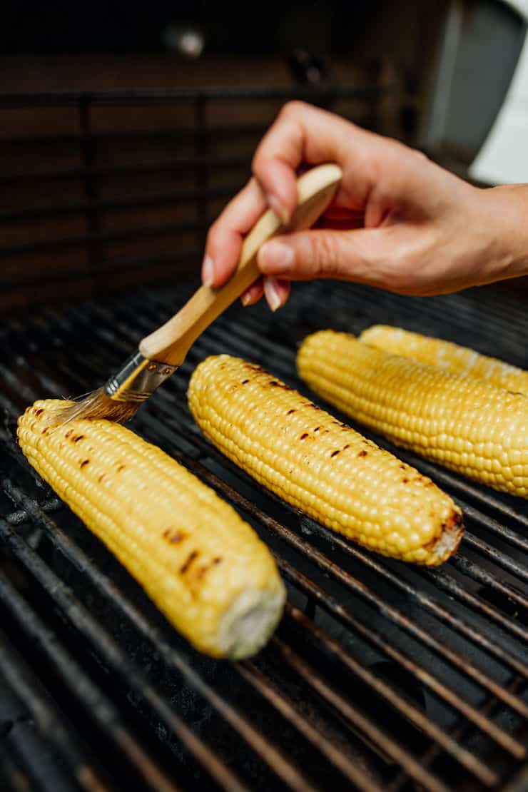 a hand brushing corn on the cob in the grill
