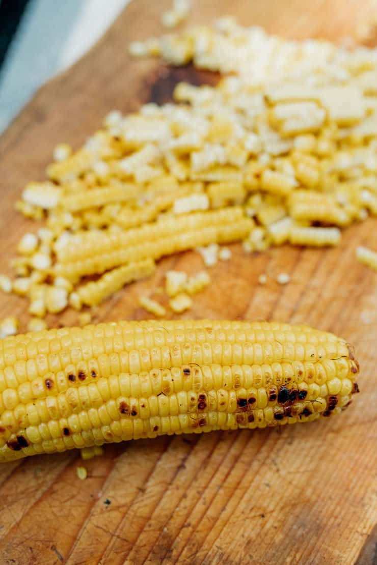 charred corn on the cob sliced on a wooden board