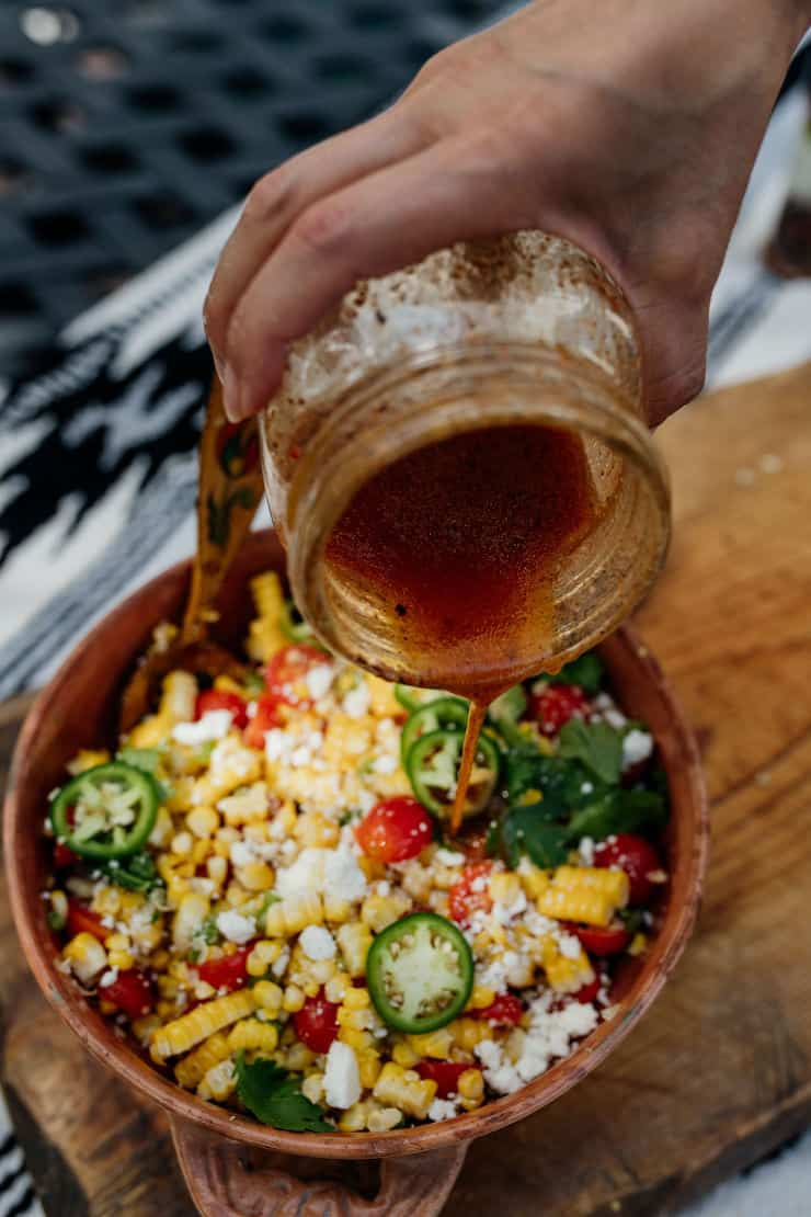hand holding a mason jar and drizzling dressing on Mexican street corn salad
