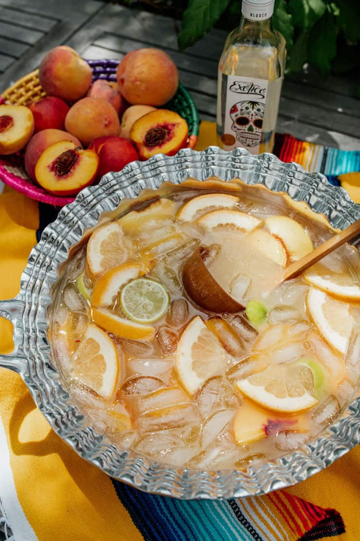 a pewter silver Mexican punch bowl filled with Paloma peach punch on a serape and basket of peaches and tequila in the background