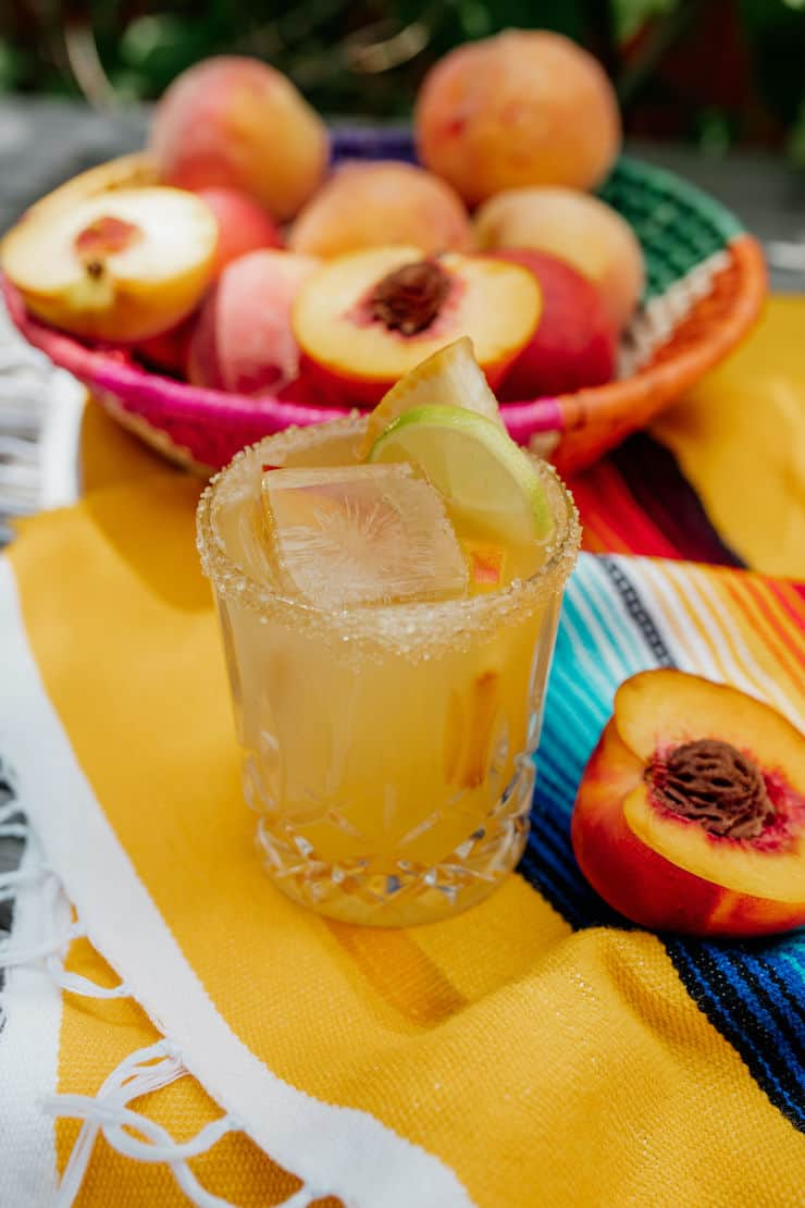 palomo peach drink on the rocks on a yellow striped serape with peaches in the background