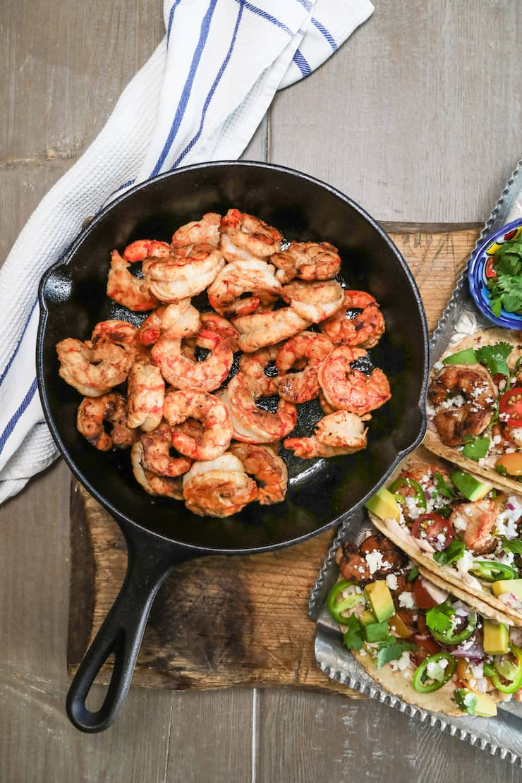 Cooked shrimp is a cast iron dish with a tray of shrimp tacos on the side