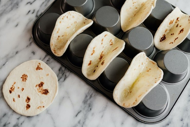 mini flour tortillas on a flipped muffin tray on a marble surface ready to bake
