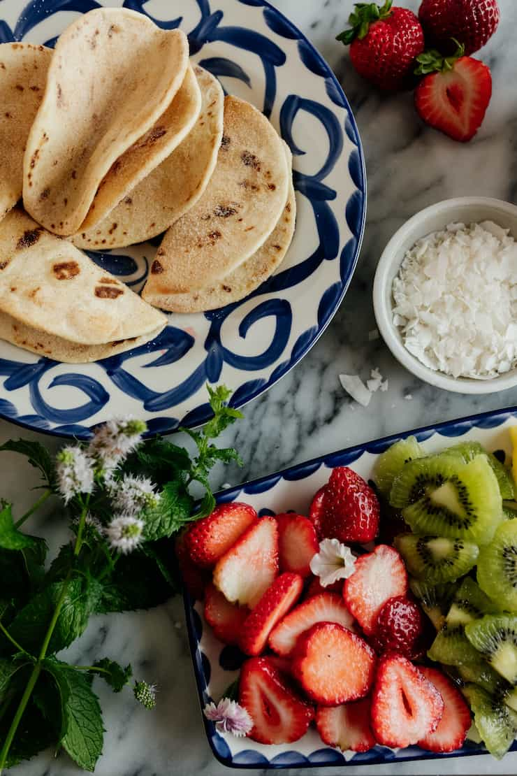 dessert tacos on a Mexican plate with a side platter of fruit strawberries kiwi dish with coconut