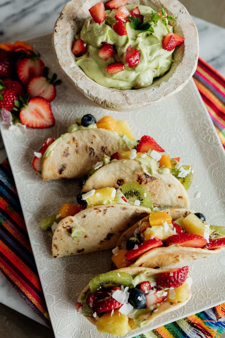 dessert tacos filled with avocado yogurt and sliced fruits and berries on a white platter