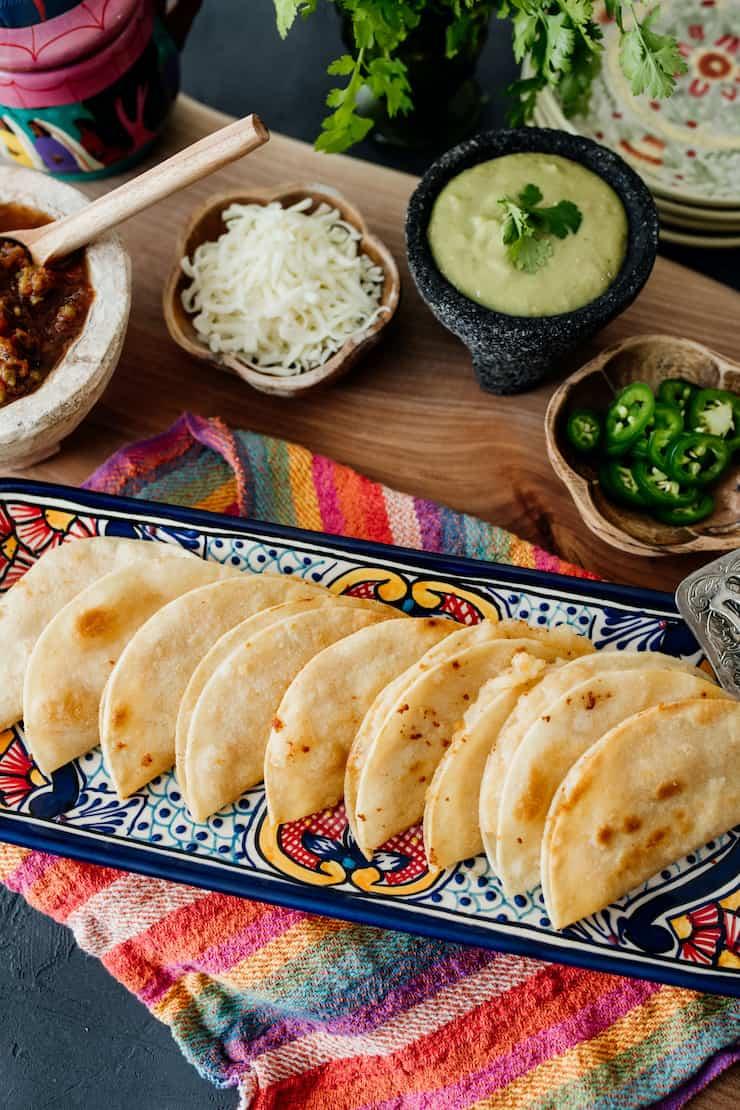 crispy vegetarian cheesy potato tacos on a platter