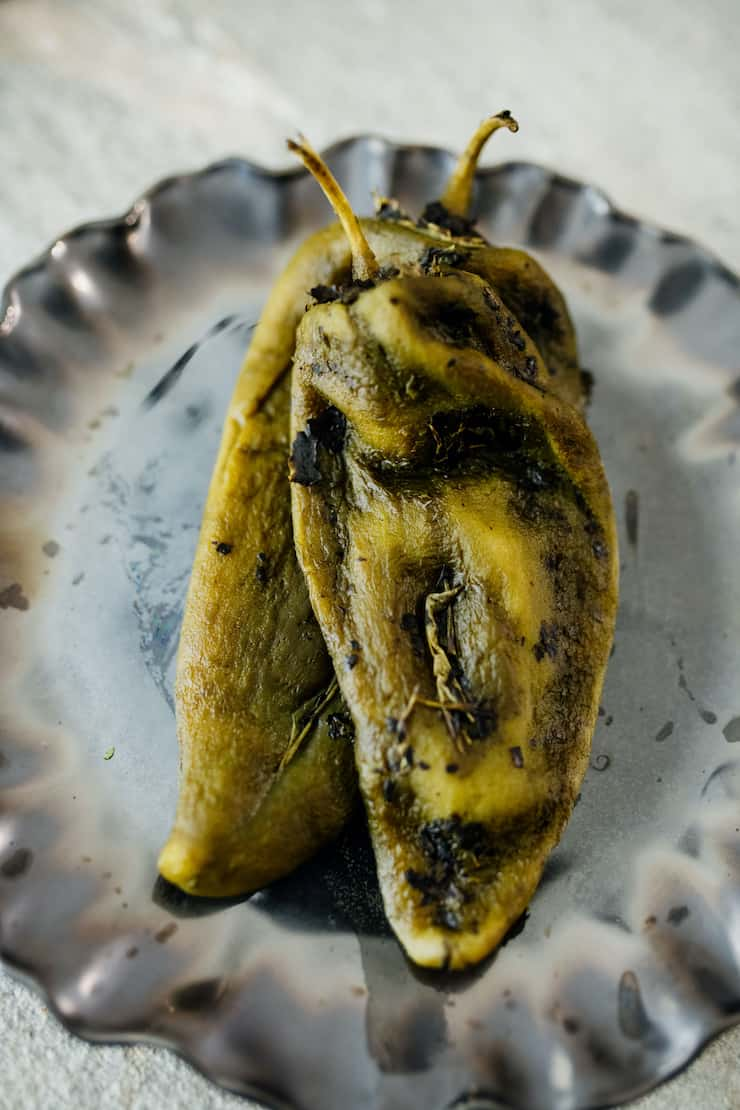 three roasted and peeled poblanos on a white and black plate