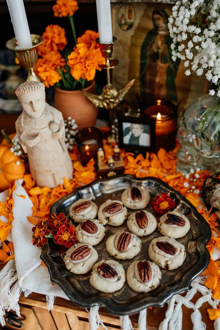 Double Pecan Thumbprint cookies on an altar for day of the dead with a patron saint Pasquale and marigolds