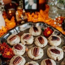 pecan shortbread cookies with marigolds in the background on a day of the dead altar