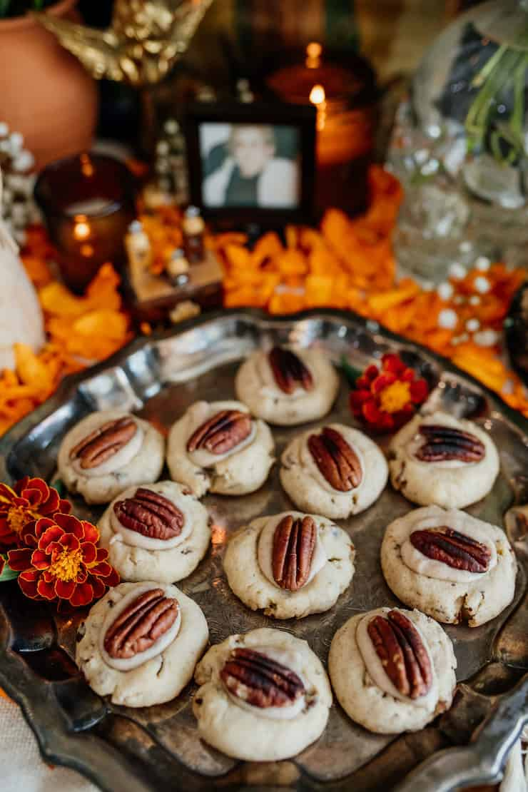Double Pecan Thumbprint cookies on a silver platter with marigolds on day of the dead altar