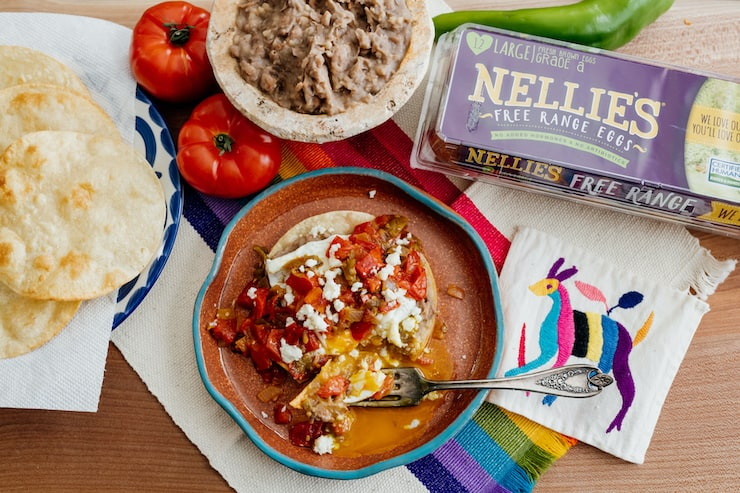 finished huevos rancheros on an earthenware plate with a silver fork on a rainbow striped placemat with a box of nellies eggs, a side bowl of refried beans, two full tomatoes and a full green pepper scattered about