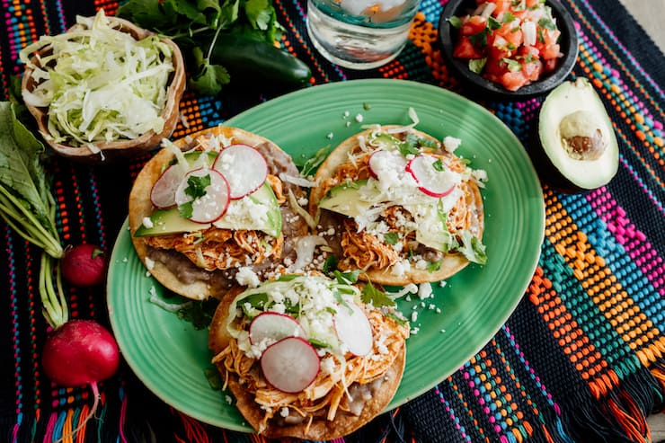 Chicken Tinga platter of tostadas on a green plate and a colorful runner and garnishes on the sides