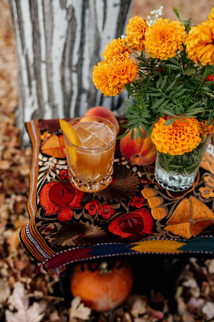 peach old fashioned cocktail in a cut crystal old fashioned glass on the rocks with a peach slice on a table with a bunch of marigolds, some fresh peaches and a striated grey and white tree trunk in the background