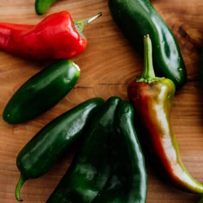 assorted fresh Mexican chiles on a wooden board