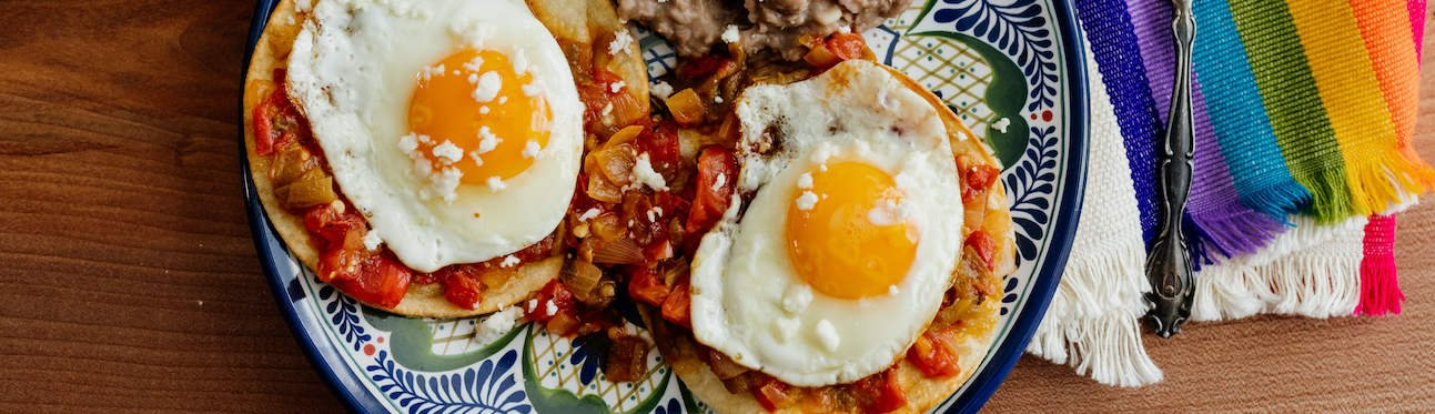 header photo of huevos rancheros on a blue and white plate on a rainbow striped cloth