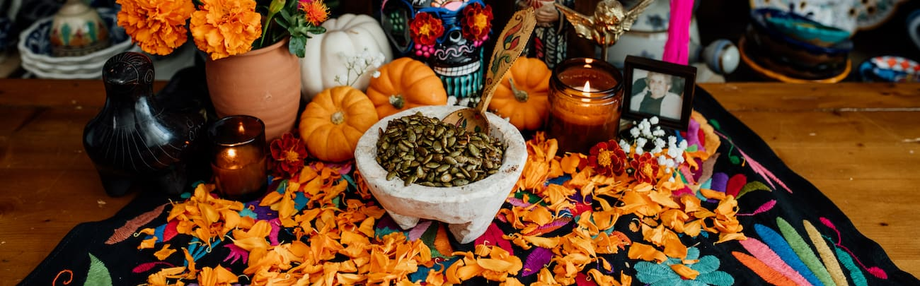 spicy roasted pumpkin seeds in a stone bowl on a dia de muertos offrenda