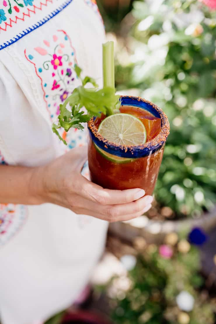 Mexican dress Latina holding a Spicy Michelada in a Mexican hand blown glass with a celery stalk and lime slice as garnish