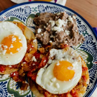 plate of huevos rancheros with a side of refried beans on a blue and white plate