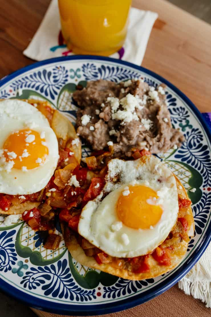 huevos rancheros on a blue and white plate with refried beans and two sunnyside up eggs