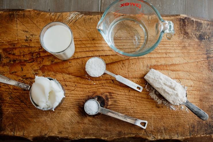 ingredients to make Gorditas de harina flour, lard, milk, water, salt, sugar on a wooden board