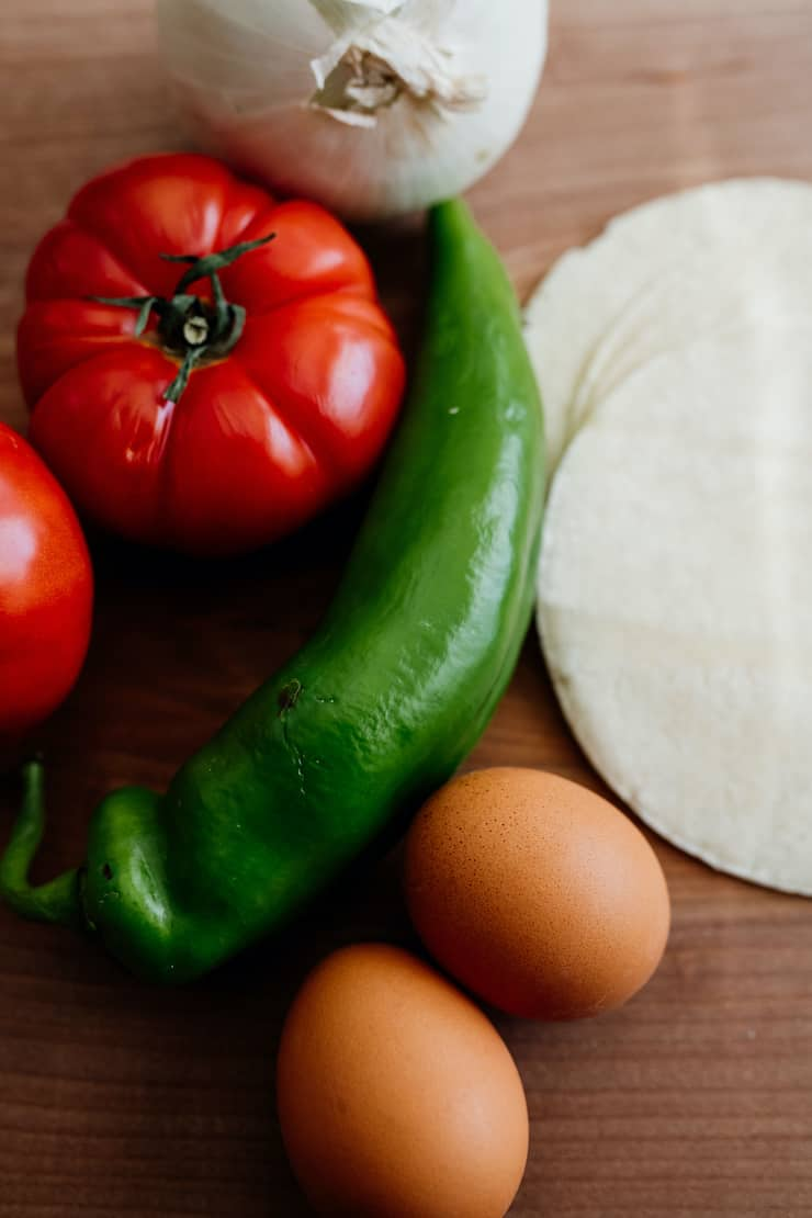 close up shot of two whole tomatoes, a green chile, two brown eggs and a few white corn tortillas