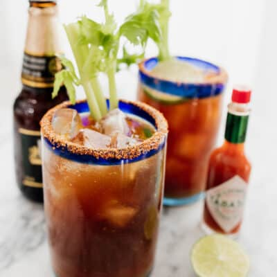 two michelada beer cocktails with hot sauce and Mexican beer