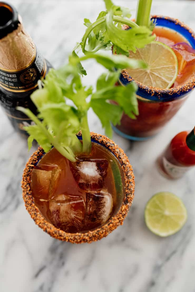 top down inside glasses of a michelada with celery stalks