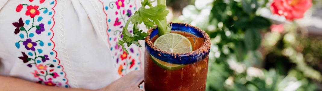 woman in embroidered Mexican dress holding a spicy michelada