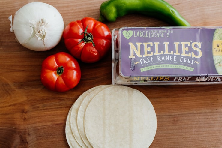 onion, two tomatoes, a green chile, a box of nellie's free range eggs and white corn tortillas for huevos rancheros
