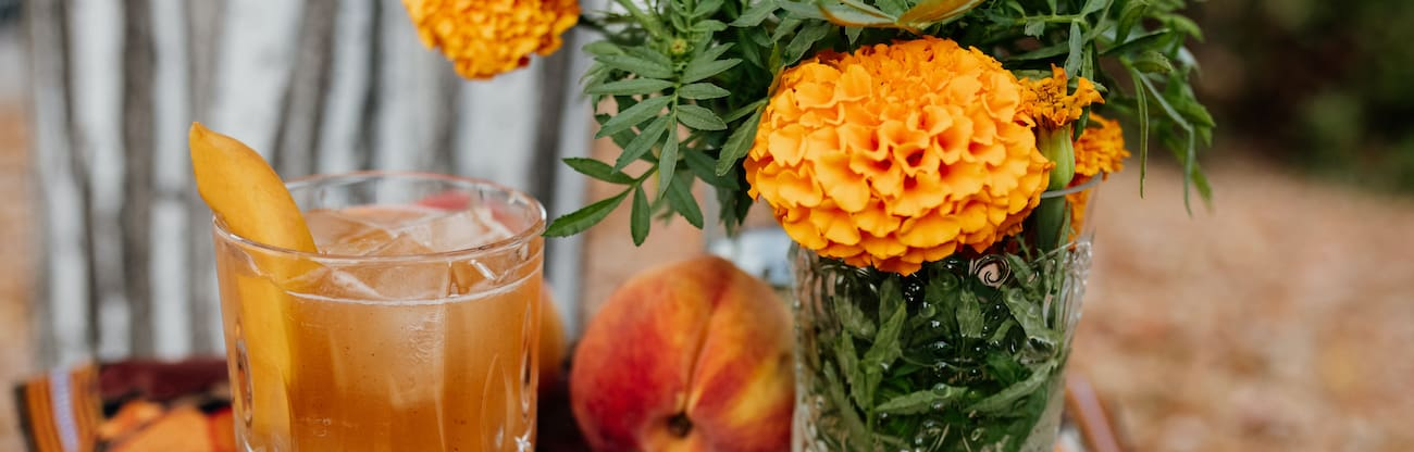 header with bourbon peach old fashioned with a fresh peach, marigolds and a striated grey and white tree trunk in the background