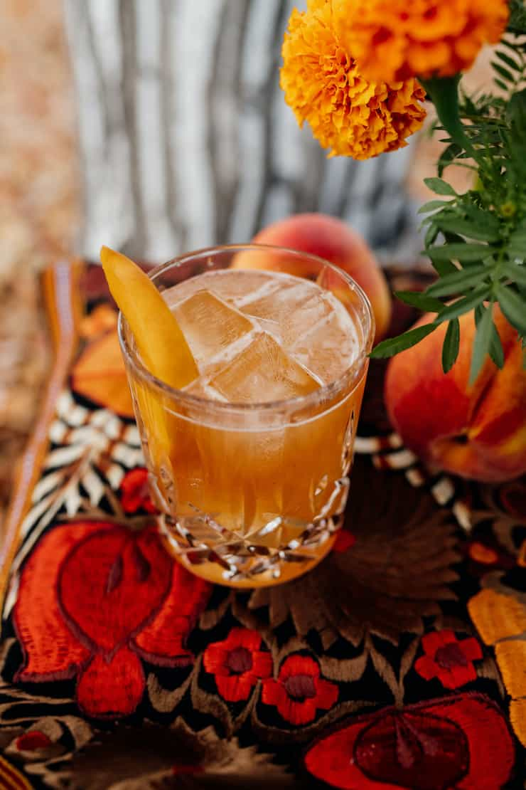bourbon peach old fashioned with a peach garnish in a crystal glass on a red and orange tablescape with marigolds
