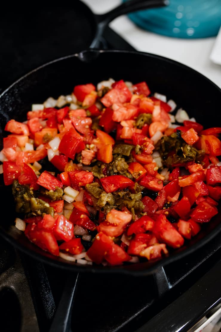 diced onions, tomatoes and roasted green chiles in a cast iron skillet