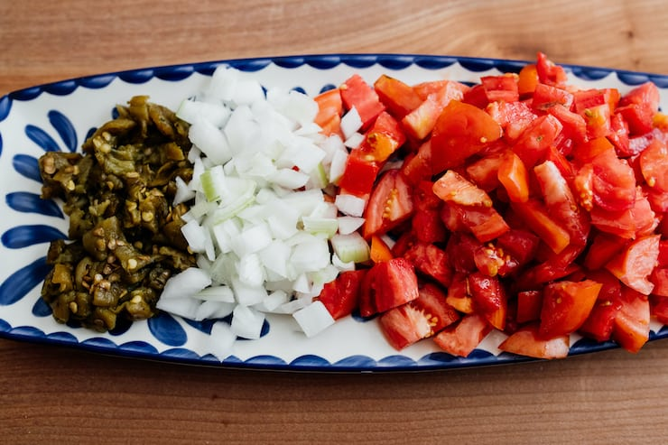 diced tomatoes, onions and roasted green chiles on an oblong blue and white plate