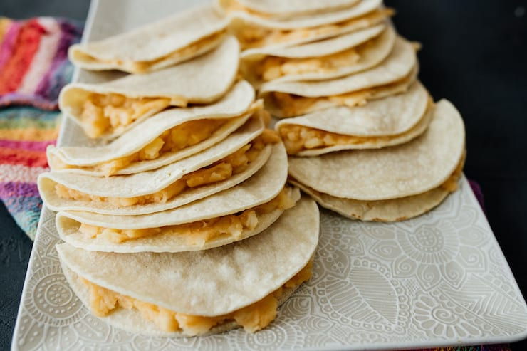 corn tortillas filled with mashed potatoes on a white platter ready to be fried for potato tacos